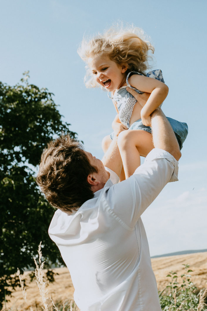 Vater hält Tochter in die Höhe