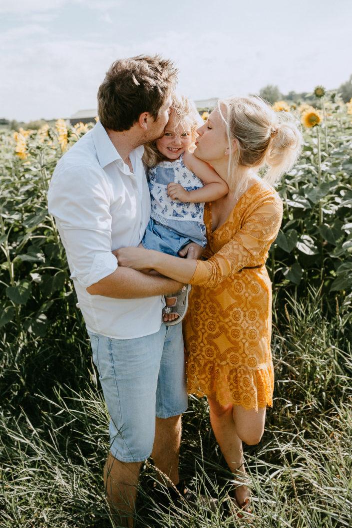 Vater, Mutter und Tochter vor einem Sonnenblumenfeld