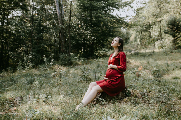 Pregnant woman in a red dress sitting in the woods